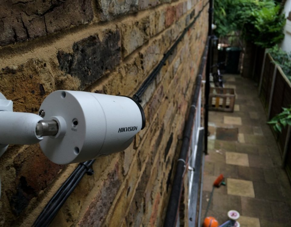 a cctv camera fitted to a house watching alleyway